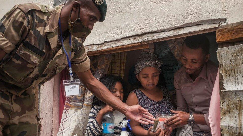 Seorang tentara membagikan masker dan sampel Covid-Organics di Antananarivo - April 2020