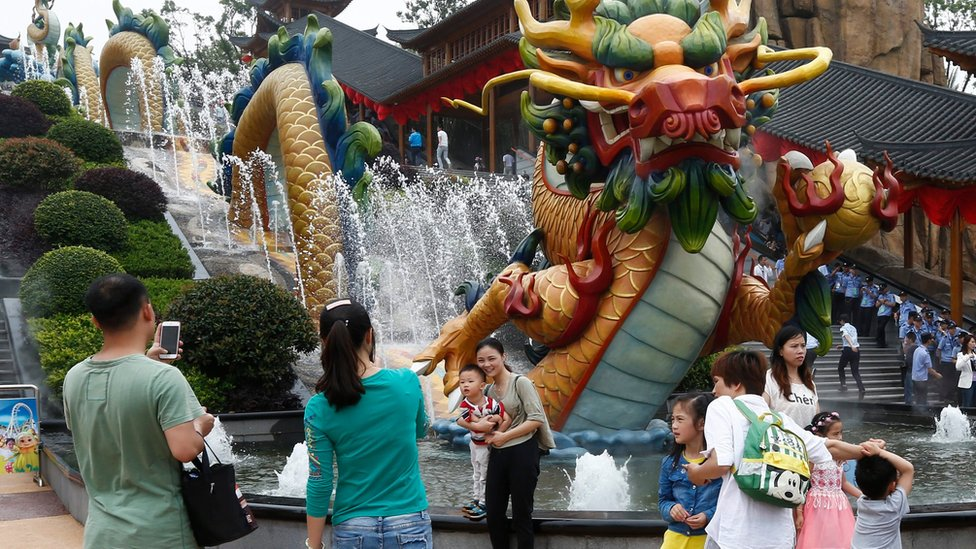 """Visitors take photos beside a dragon fountain at an outdoor theme park of the newly-opened Wanda Cultural Tourism City or """"Wanda City"""" in the eastern city of Nanchang in Jiangxi Province, China, 28 May 2016"""