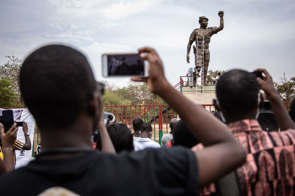 People take photos of the second bronze statue of Burkina Faso's former President Thomas Sankara on17 May 2020.