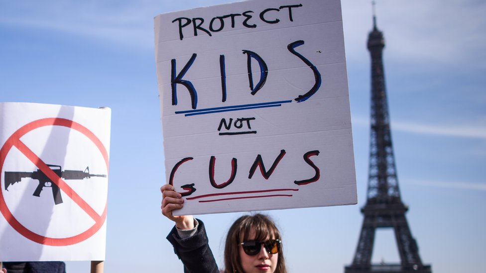 """A woman holds a poster which read """"Protect Kids not Guns"""" as French and Americans gather near the Eiffel Tower on the Trocadero square in support of the US """"March For Our Lives"""" movement, in Paris, France,"""
