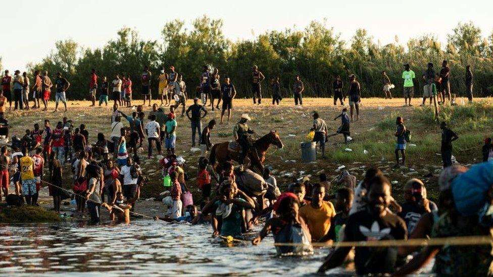 Agentes fronterizos a caballo rodeados de migrantes