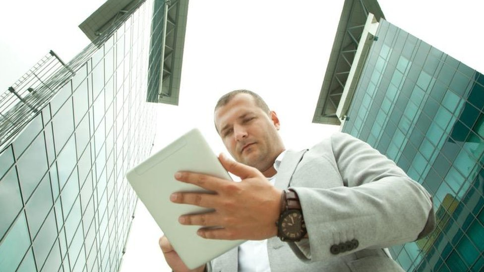 Man with tablet outside buildings