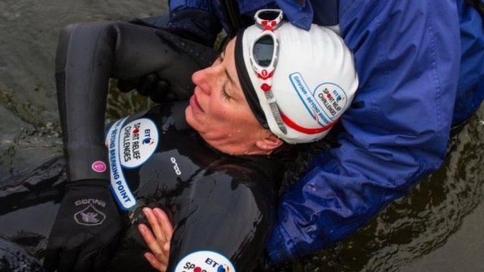 A apresentadora Davina McCall respira cansada após completar parte do percurso nadando