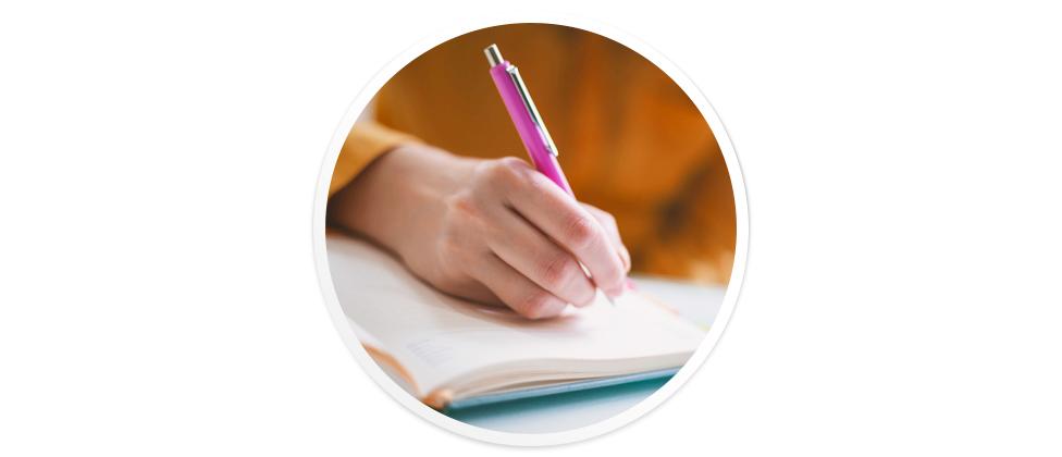 Tangan menggenggam pulpen.