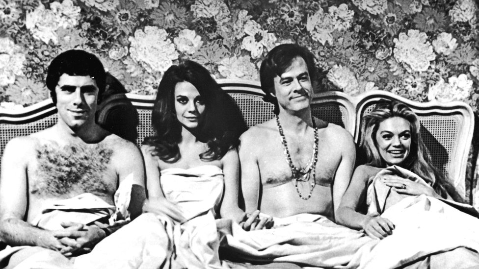 American actors Elliott Gould, Natalie Wood, Robert Culp and Dyan Cannon sit in bed together in a promotional still from the film, 'Bob & Carol & Ted & Alice,'