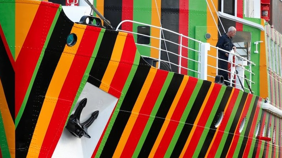 A man stands on the deck of the brightly painted former pilot ship The Edmund Gardner at the Albert Dock in Liverpool, northern England, June 11, 2014.