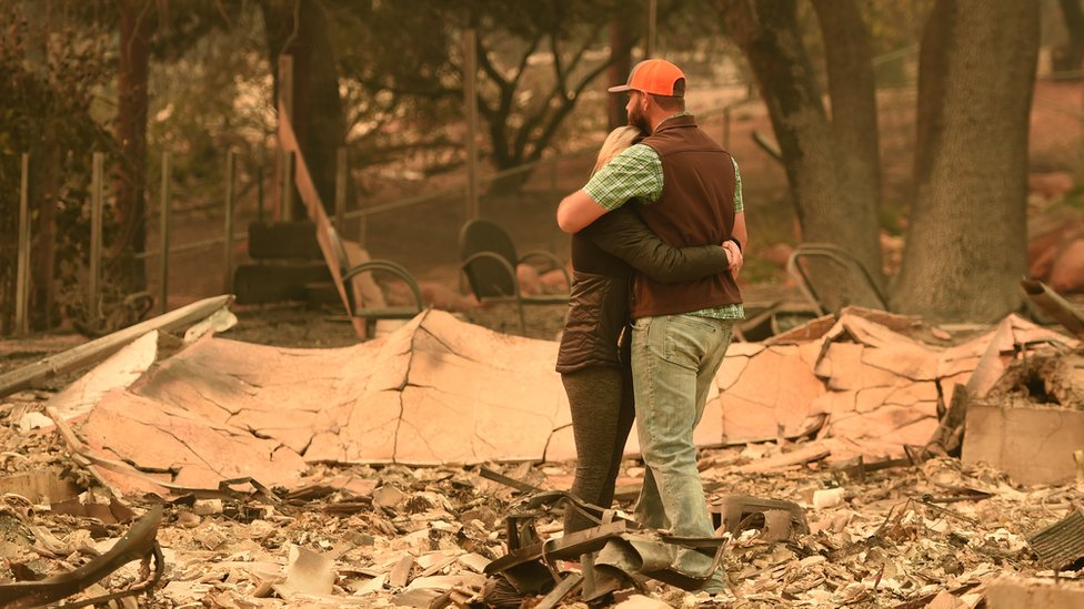 A couple hug in wreckage of home