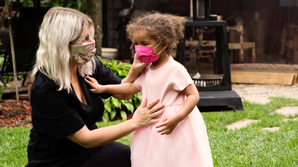 A woman and child in face coverings