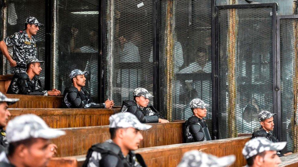 أعضاء من جماعة الإخوان المسلمين خلف القضبان أثناء محاكمتهم في العاصمة القاهرة في 28 يوليو/تموز 2018