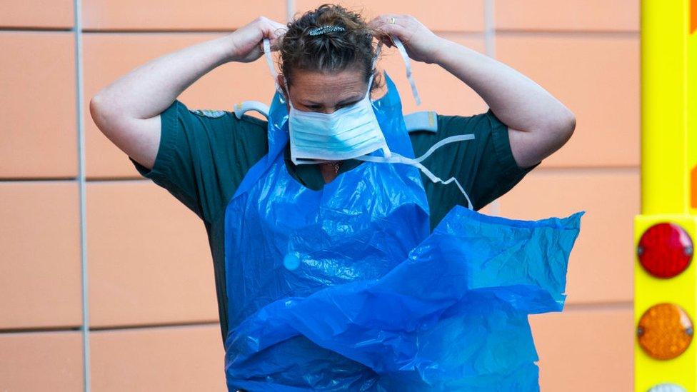 Un trabajador de la salud se coloca equipo protector para la pandemia.