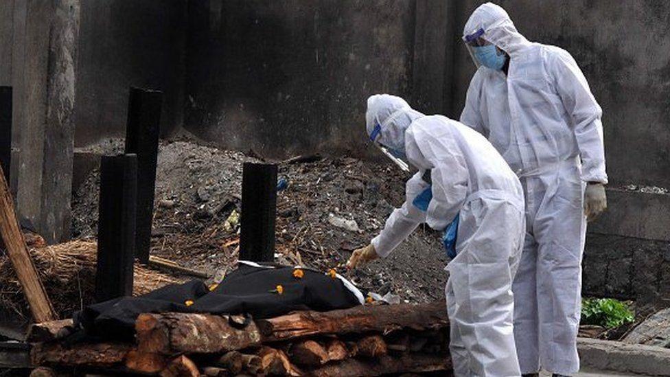 عاملان طبيان بجوار جثة أحد الموتى