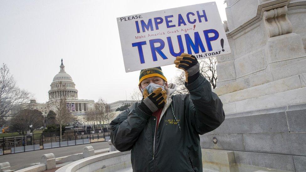 Un hombre sostiene un cartel en el que pide que se haga un impeachment a Trump