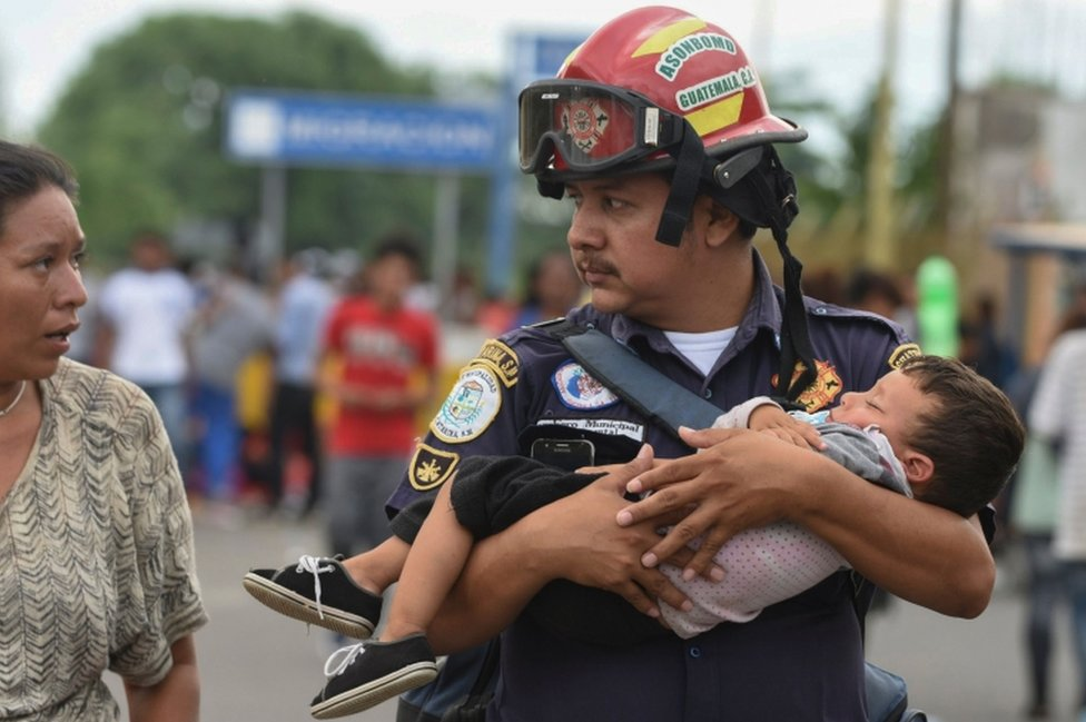 A Guatemalan firefighter carries an ailing toddler while speaking to a woman, possibly the boy's mother