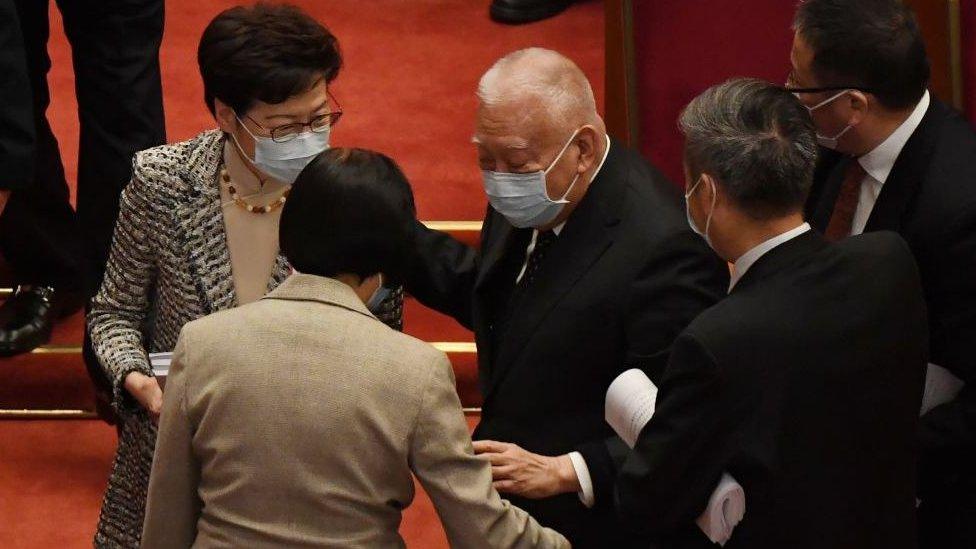 全國政協副主席、香港前行政長官董建華在北京人民大會堂列席人大會議後跌倒,眾人攙扶。