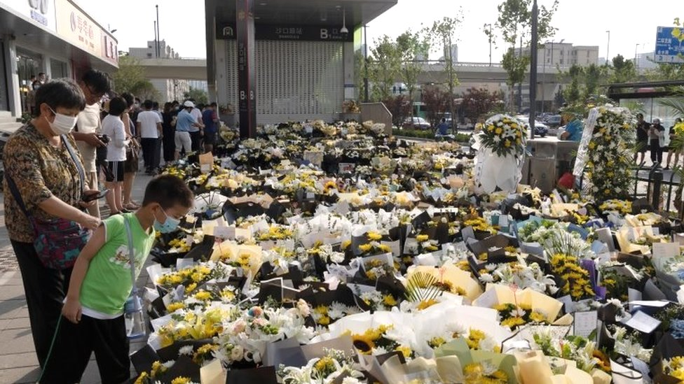 People stand next to flowers placed at an entrance to a subway station in Zhengzhou