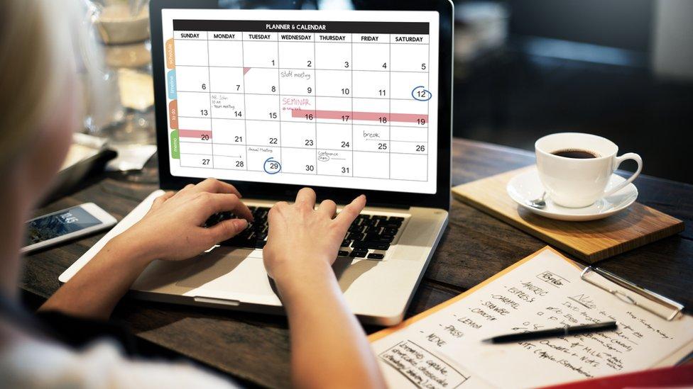 Una mujer escribe en un calendario en su computadora.