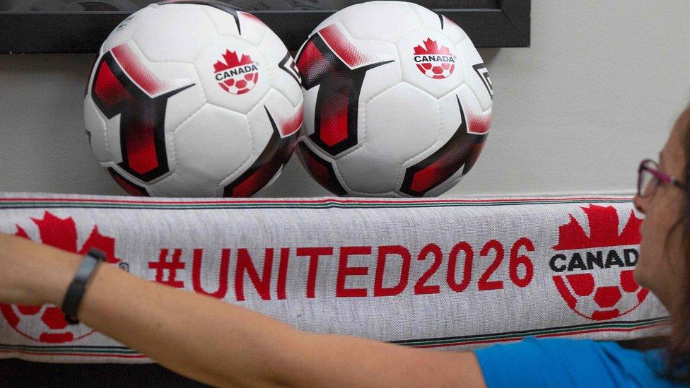 Una mujer junto a dos balones y una bufanda de la candidatura de Canadá al Mundial