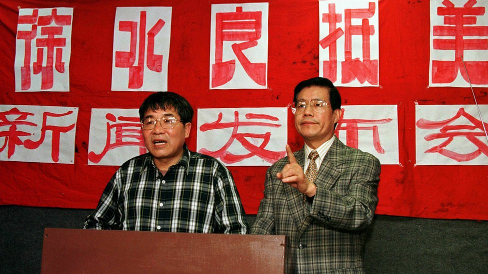 Xu Shuiliang (L) answers questions from reporters 01 April at a news conference in Queens, NY. The sign in the back announces that the exiled Xu has arrived in the US. At right is a spokesman for the Chinese Democracy and Justice Party Wang Bingzhang.