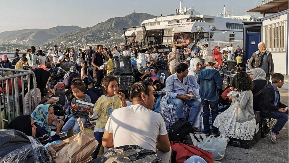 Refugees and migrants wait to board a ship at the port of Mytilene, in the island of Lesbos on September 2, 2019.