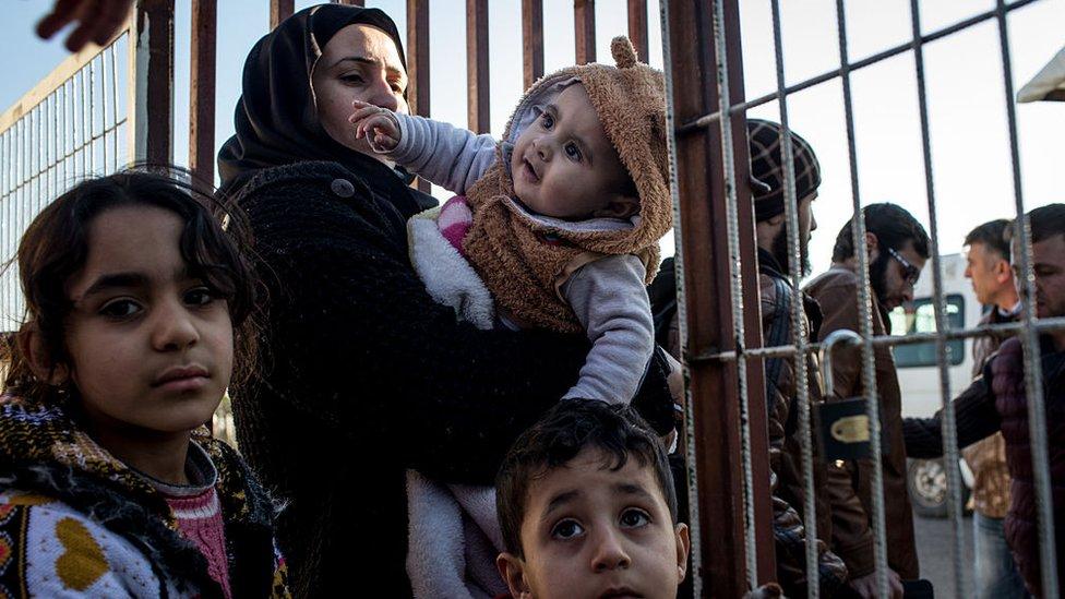 Jóvenes y adultos en la frontera turca.