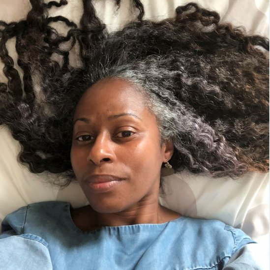 Shelli lies on a bed with her long hair splayed and grey visible at front