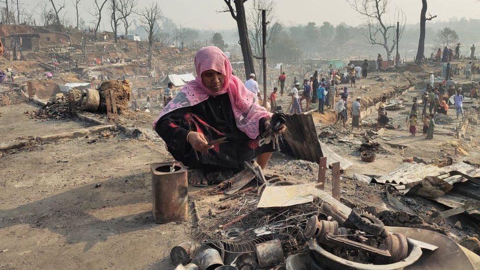 امرأة تلتقط ما تبقى من النار من ممتلكاتها