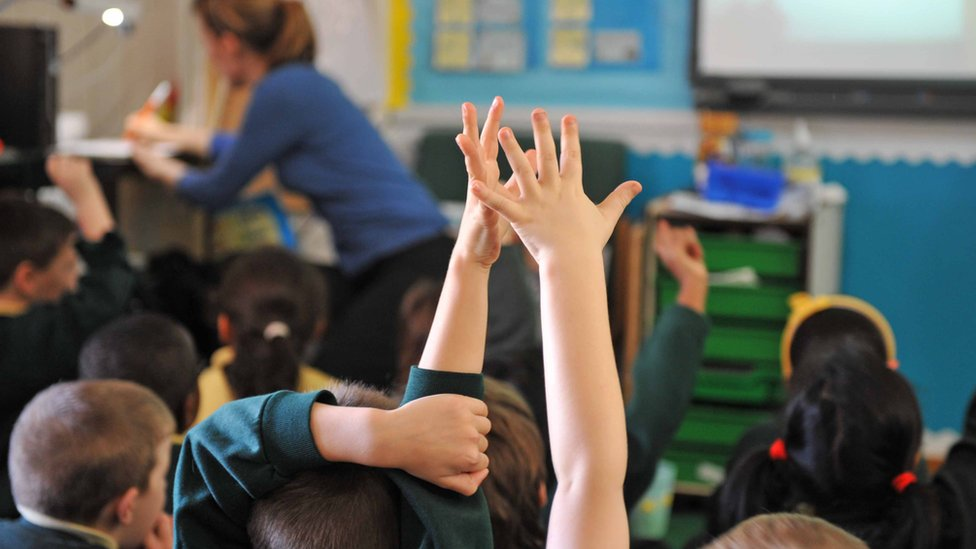Children in a classroom with hands up
