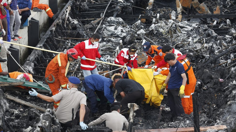 Workers remove bodies of those who died from the ferry on 1 January 2017