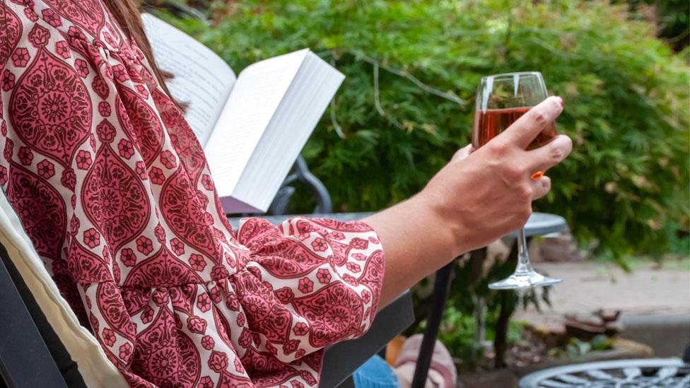 A woman drinking in a garden