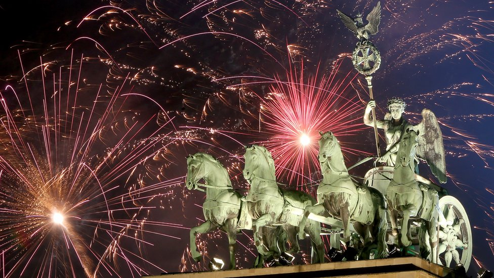 The Brandenburg Gate - a winged chariot rider with four horses - is seen in front of a sky filled with fireworks