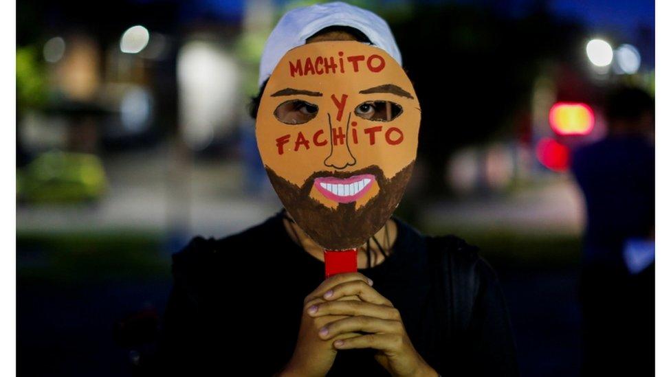 """En una protesta contra medidas adoptadas por el gobierno de El Salvador, un joven hace alusión al presidente, Nayib Bukele, con una máscara que dice """"machito y fachito""""."""