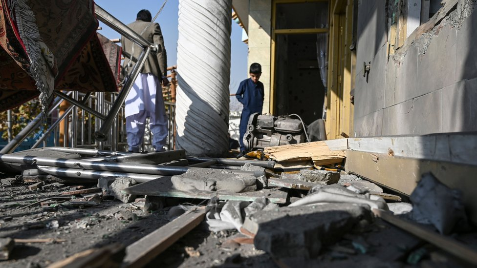People inspect a damaged house after several rockets land at Khair Khana