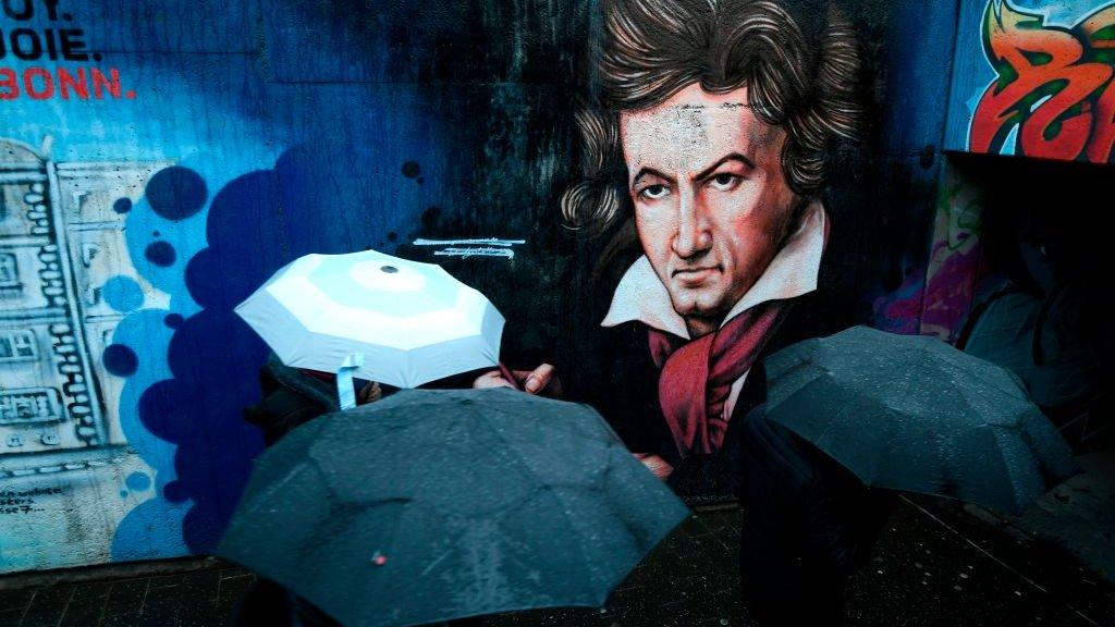 Paraguas de gente que pasa cerca de un grafiti de Beethoven en su ciudad natal de Bonn.