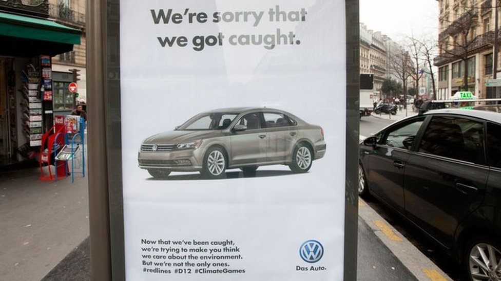 """A poster parodying Volkswagen reads: """"We're sorry that we got caught."""""""