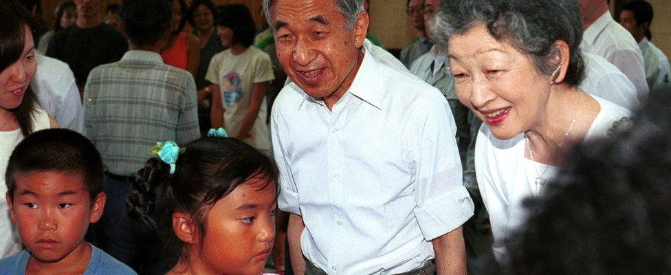 Emperor Akihito and Empress Michikos peak to local children on a visit to Niijima Island in the Izu island chain, south of Tokyo - July 2001