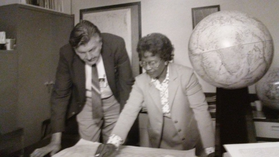 Gladys West in an office working with a male colleague