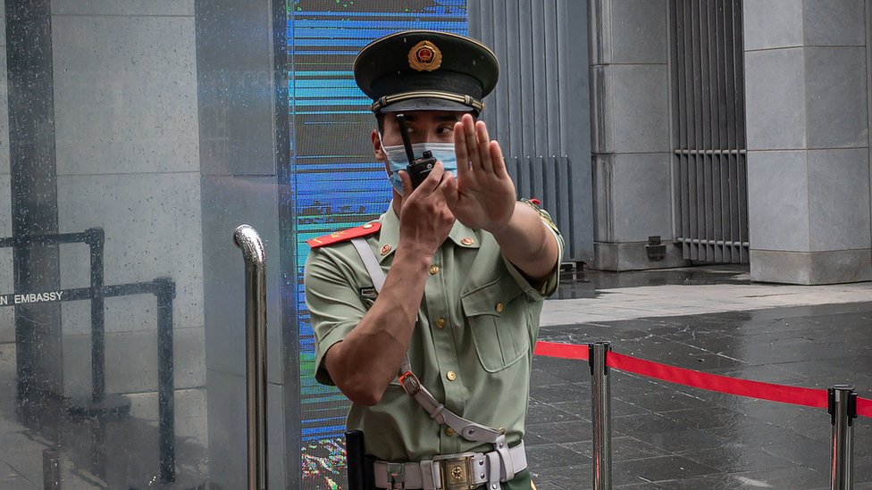 "A Chinese police officer gestures ""stop"" outside the Australian embassy in Beijing in July 2020"