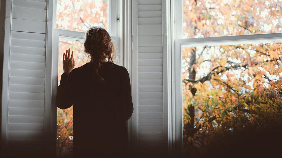 devojka gleda kroz prozor
