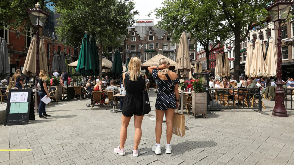 Women wait to sit down outside cafes in Amsterdam