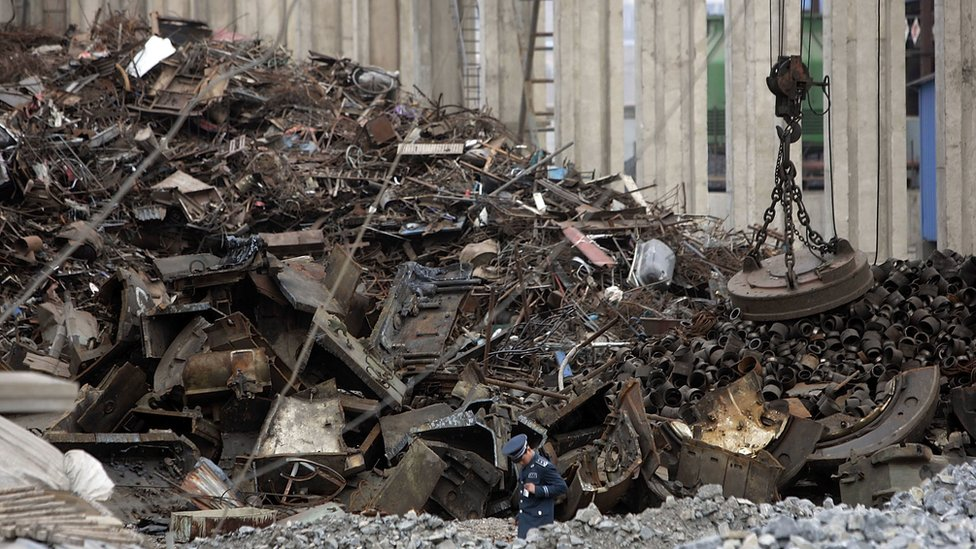 A security guard walks past a vast pile of scrap metal outside the Qinghe Special Steel Corporation plant