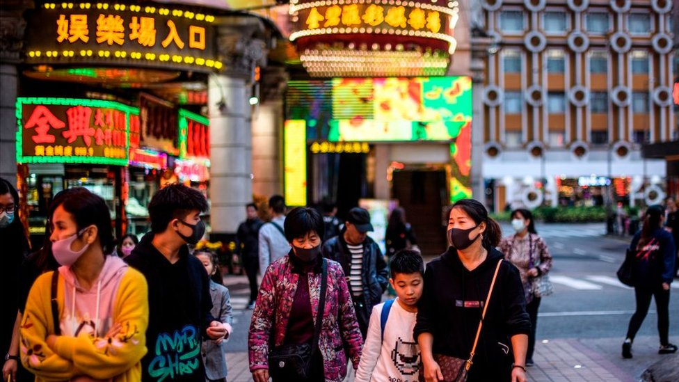 Imagen de personas caminando por una calle de Macao con carteles luminosos de fondo.
