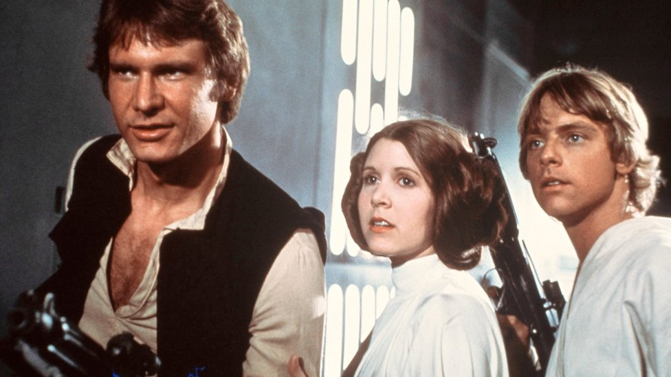 Carrie Fisher (C), with Harrison Ford (L) and Mark Hamill in the first Star Wars film