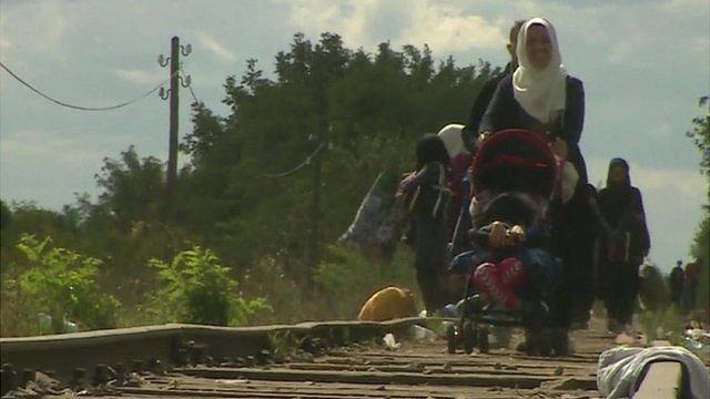Migrants walking on railway line