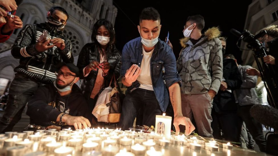 People lights candle outside the Notre-Dame de l'Assomption Basilica in Nice on October 29, 2020