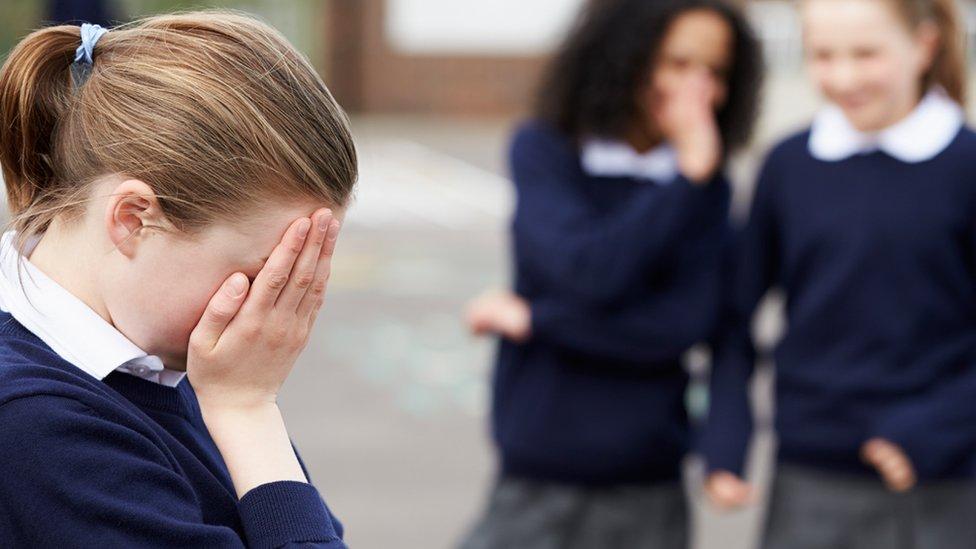 Школярка закрила обличчя руками, позаду неї пліткують дві інших дівчинки