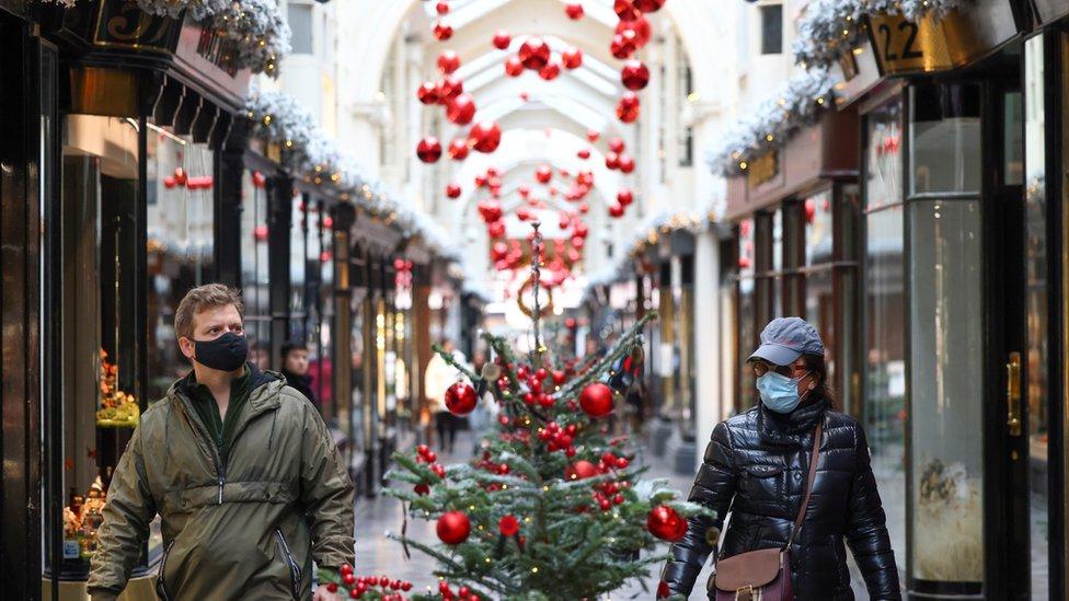 People walk through the Burlington Arcade adorned with Christmas decorations