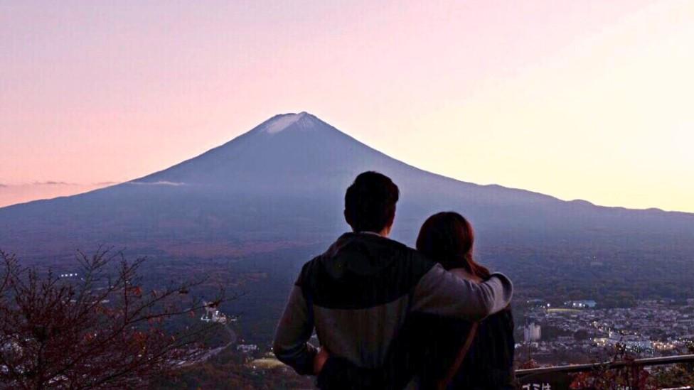 Pareja abrazada en un atardecer observando una montaña a la distancia