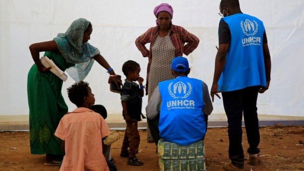 سيدتان وأطفال إثيوبيون مع عامل من المفوضية السامية للأمم المتحدة لشؤون اللاجئين