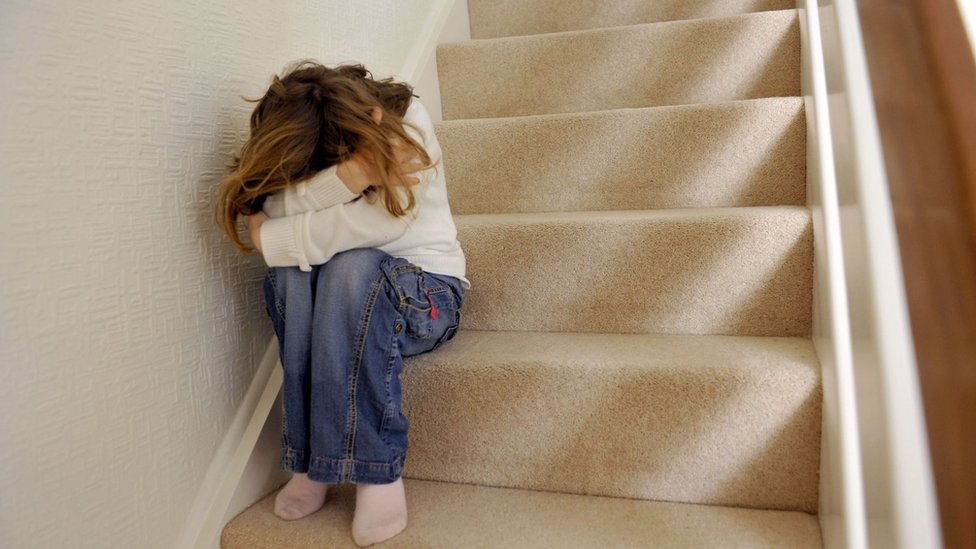 Young girl sitting on stairs with her head in her hands