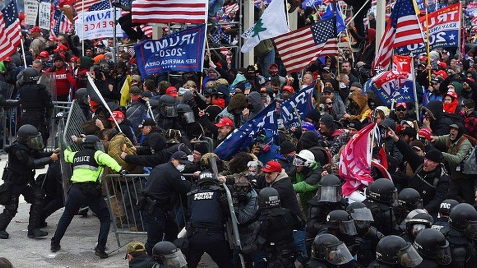 Un grupo de policías intenta contener a miles de manifestantes que intentan ingresar al Capitolio.